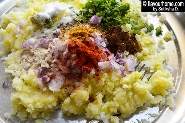 adding spices to the potatoes stuffing for aloo paratha